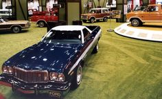 1974 Ford trucks at the Chicago Auto Show. Seen in a 7/8 front view, is the stylish two-toned Ranchero two-door car/pickup truck, inside of Ford truck exhibit. A portion of an F-150 pickup truck can be seen on the raised platform on the right. Mid-photo, to the right of the center column, is a Bronco.