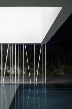Placid waters, a calm pool and framed by white linea structure   The white gallery house - Pitsou Kedem Architecture