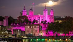 Breast Cancer Awareness in the UK: The Union Flag flies over the Tower of London which looks unusually serene in the fuchsia glow