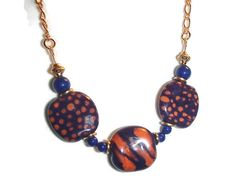 Three beautiful Kazuri beads in shades of midnight blue and a deep burnt orange shade make this a very special set. On the necklace, the Kazuri beads include two with dots and one with a patterned design. The beads are spaced with dark blue Swarovski glass pearls and bright brass spacers. The necklace is finished with two lengths of gold plated chain. The necklace closes with a lobster clasp. The length of the necklace is about 18 inches in length The earrings are made with two midnight…