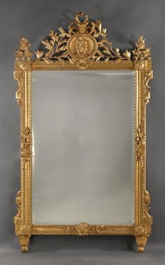 A Fine Louis XVI Style Carved Giltwood Mirror, the Cresting Carved With a Portrait Roundel of a Young Woman in Profile.  This impressive mirror is richly carved with a ribbon tied laurel cresting centred by a guilloche framed roundel, carved with a portrait medallion of a young woman in profile. The cresting is flanked by foliate terminals above uprights carved with guilloche running pattern and foliate sprays, framing a rectangular bevelled mirror plate. - Adrian Alan