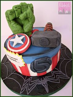 Avengers birthday cake with Hulk fist, Thor hammer, Captain America and Venom, comic book style by Bibbidi Cake Co.