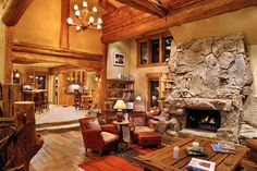 Unique Stone Fireplace in Traditional Living Room using Luxury Log Home Plans with Brown Sofas and Wooden Table