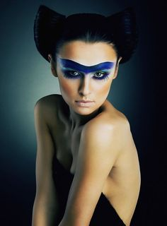 Interesting use of blue on forehead & lower eye lashes. The hairdo has a possible bat design?