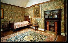 """Honeysuckle"" (1876) wall hangings designed by May Morris, daughter of William Morris. The room holds 2 Morris & Co. ""Sussex Chairs"", an armchair & corner chair (at foot of the bed). A ""Small Barr"" Hammersmith (carpet) designed by William Morris, graces the floor at Wightwick Manor, Wolverhampton, West Midlands."