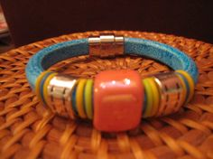 Blue licorice leather bracelet w/ pink-orange ceramic bead,  yellow, lime green and blue rubber o-rings, silver 'stiched' spacer beads . on Etsy, $35.00
