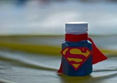 for NICK! Superman Bubbles! Buy a pack of small bottles of bubbles. You can usually find them on wedding party supply sites. Cut small pieces of red fabric  for the capes, add a drop of food dye to the bubbles to make them blue, and use a Cricut and the Superman template to make the emblems. Hot glue the emblems and the capes.