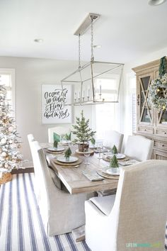 A neutral Christmas dining room with a navy blue striped rug, linen chairs, reclaimed wood dining table, Darlana linear pendant light fixture and woodland coastal decor.