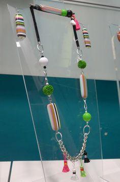 Velluto tubolare elasticizzato, resine lunghe a righe, catena piatta e nappe multicolor per questa collana lunga.