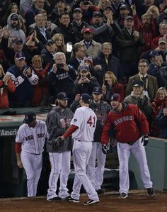 Boston Red Sox starting pitcher John Lackey (41) is greeted by teammates after being taken out during the seventh inning of Game 6 of baseba...