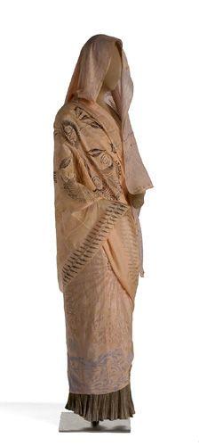 Falda (Delphos); Velo (Knossos) Falda (Delphos); Velo (Knossos) Falda larga de seda plisada en color gris y velo rectangular llamado Knossos. Sobre fondo rosa salmón, se dispone una decoración con motivos vegetales y geométricos en color azul, rosa y negro. 1906-1930 (ca) Dación de INDITEX S.A., 2003 INVENTARIO: MT88443; MT88479 Este tipo de velos fueron bautizados por Fortuny con el nombre de Knossos, por estar inspirados en el himation griego y ornamentados con los motivos del repert...