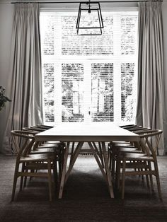 Floor-to-ceiling windows in a lofty dining room with horizontal blinds and a simply designed wood dining table surrounded by Wegner chairs