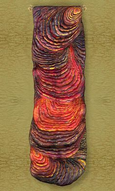 """This is Pele' by Petra Voegtle, using her own technique of """"silk carving.""""   """"The surface of the fiber was transformed completely into a relief. The upper layer of this piece was made from one single piece of silk - nothing was sewn on top to add depth. Additionally paints and pigments were used in a manner to give the visual impression of flowing lava in all its glowing colours and the viewer is supposed to feel the heat. But it is 'only' a piece of soft sculptured silk."""""""