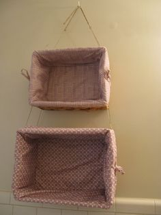 Hanging baskets for bathroom storage. - Since I rent I didn't want to put too many holes in the wall. I found these baskets for $20. The fabric is taped in place with Res-Q (fabric) tape. I used hemp twine from the craft section of Walmart. I hung the whole thing on a single cup hook.