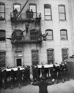 """Fire Department Tryouts 1935  """"Behind the scenes as rookies become smoke eaters. Before they become full-fledged members of the NYFD, training in the art of fighting the fire menace, at the Department's training school. the above photo shows a pair of recruits leaping into space to life nets below, from the second story window. Others wait to follow suit.""""  From Bettmann Corbis  Shared by nyfirestore.com/  Being pre-scba, George's dad is VERY proud to be a true """"smoke eater""""!! :^)"""