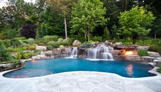 Custom volcanic fire pit inground swimming pool waterfall idea