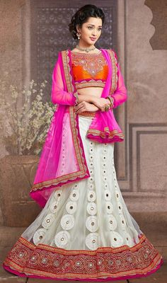 Designer off white net lehenga with contrast choli and dupatta makes perfect combo for evening party requirement. The A-line lehenga is embellished with silk thread embroidery on contrast orange and pink border, thread work, pearls and traditional Gujarati mirror work which gives you grand and exquisite look. The contrast pink net dupatta has scalloped shape lace and silk thread embroidery on contrast orange border. #LatestIndianTraditionalCholi