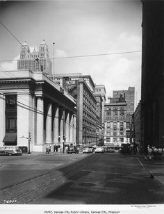 View looking east down 10th Street, taken from the 10th and Baltimore intersection in downtown Kansas City, Missouri. The First National Bank (later home to the Central branch of the Kansas City Public Library) is visible on the left as well as the Fidelity Building twin towers. The Victor Building can be seen next door to the bank and a Rothschild's sign across the street. July 13, 1953.