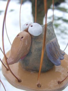 Modrošedý ptáček v kleci Keramický pták - vypálený ze světle hnědé keramické hlíny, lehce kolorovaný modrošedou a fialovou engobou, hrubý povrch bez glazury. Pouze zobák, dno klece a konce křídel jsou naglazovány lesklou bezbarvou glazurou a oči lesklou bílou. Klec je z 0,8 mm silného drátu měděné barvy, dá se zavěsit i postavit. Pták je vysoký cca 4,5 cm, klec má ...