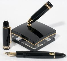 """MONT BLANC 'MEISTERSTUCK' RESIN FOUNTAIN PEN WITH 18KT GOLD NIB & INKWELL, NO. 149, L 5 3/4"""":Including 1 black resin fountain pen with gold plated clip and rings and an 18 kt gold and platinum inlaid nib, marked """"1810 (trademark) Mont Blanc 750 STod"""". One band around the cap is marked """"XY2510984"""" and the other is marked """"Mont Blanc Meisterstuck No. 149""""; the band on the holder of the inkwell is marked the same."""