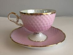 This is a beautiful teacup with delicate gold feet. The inside of the cup is pearl colored with beautiful pink roses. Roses decorate the saucer as