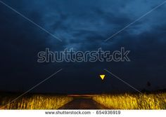 Stormy clouds over a field with give way sign