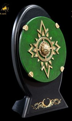 Rohirrim Royal Guard Miniature Shield Prop Replica from Lord Of The Rings. It is made by WETA and is approximately 6 cm (2.4 in) diameter  http://tolkien.minimodelfilmstuff.co.uk/tolkien-collectable/lord-of-the-rings-the-two-towers-rohirrim-royal-guard-miniature-shield-replica-weta-wt00797  As the protectors of the Golden Hall of Edoras, the Royal Guards of Rohan were issued with regal uniforms of scale and plate as well as richly endowed weapons and shields. The green colour dr...