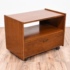 This small media center is featured in a wood with a glossy cherry veneer. This contemporary entertainment center has a rolling wheel base, a large drawer and interior cubby space. Great as a nightstand of tv stand! #contemporary #dressers #nightstand #sandiegovintage #vintagefurniture
