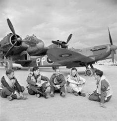 Pilotos británicos tomándose un descanso en el aeródromo de Luga, isla de Malta; nótese el bombardero medio Beaufighter y el caza Spitfire Mk5 C tras ellos, enero de 1943