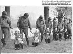 American soldiers escort a group of Dutch children after the liberation of the Netherlands, to a folk song concert (February, 1945)
