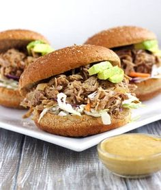 These chipotle slow cooker pulled pork sandwiches are topped with creamy avocado ranch sauce. A quick and easy, kid friendly dinner! Click for the recipe! #Foodfaithfitness #Chipotle #Slowcookerpulledpork #Dinner #Kidfriendlyrecipe
