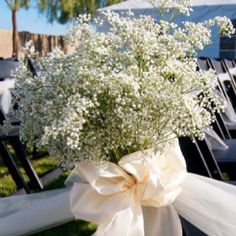 Baby's breath and ivory satin and tulle pinned on the aisle chairs.