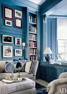 A beautiful and bold blue library and reading nook, decorated with blue and white patterned pillows, Chinoiserie, lamps, artwork and gilded sculptures. Love this modern twist on traditional!