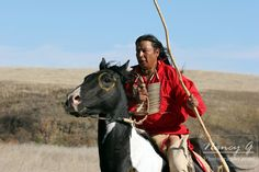A Native American Sioux man riding horseback on a NA horse with a coup stick in the Plains of South Dakota. Nancy Greifenhagen Photography