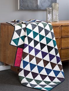 This eye-catching project features alternating jewel-toned batik and off-white 60° pyramid units. Use the Fons & Porter 60° Pyramids Ruler for easy cutting. Digital pattern and quilt kit available!
