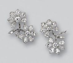 PAIR OF DIAMOND EARCLIPS, VAN CLEEF & ARPELS. Each designed as a pair of blossoms, altogether set with 24 pear-shaped, 20 baguette and 4 round diamonds weighing a total of approximately 10.25 carats, mounted in platinum, signed Van Cleef & Arpels, numbered 19526.