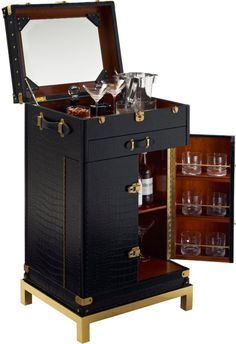 The One Fifth Trunk Bar from Ralph Lauren Home @Ralph Lauren  (on display at our St. Louis showroom) is a Pullman style trunk bar with embossed crocodile leather and polished brass stand features a mahogany interior and a mirrored back panel. Includes barware stowage, mixing surfaces and custom fitted wells.