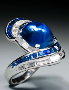 A late 1930's sapphire and diamond ring, centered by a cabochon sapphire weighing approx 9,67 ct., surrounded by calibré cut sapphire and diamond swirls, mounted in platinum.