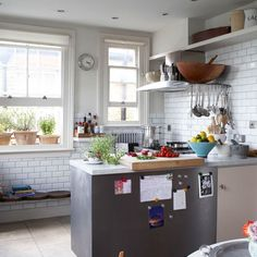 Urban-style kitchen The white tiles and stainless-steel cladding give this kitchen a contemporary look. The African bench and wooden cookware tone down the modern element. Tiles Fired Earth Worktops Surrey Marble & Granite Bench The Conran Shop