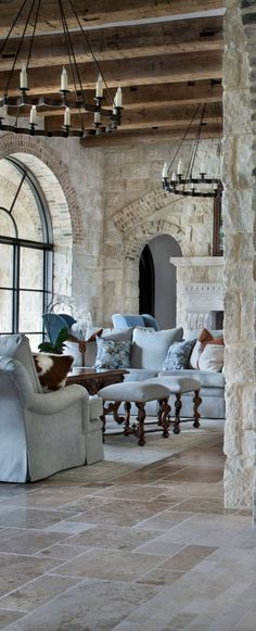 luxury rustic living room. stone walls with brick soldier rows, wood beam ceiling, London arm chairs with waterfall skirt. Turned leg ottomans. light blue upholstered furniture. DesignNashville.com lighting, designer fabrics, custom draperies and furnitur (Outdoor Wood Beams)