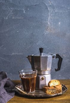 Glass espresso coffee on rustic wooden board, cantucci biscuits and steel Italian Moka pot