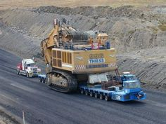 massive excavator being towed by a 128 wheeler truck
