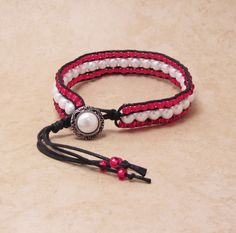 6mm White faux pearls framed with red glass beads make this thin cuff a delight to wear.    The materials used are cotton cord and Fireline for added strength. The button is silver tone metal with imitation pearl.    Fits comfortably from a 7 to 7 3/4 inch wrist    This bracelet is an ideal gift idea for your special lady!    $18.00