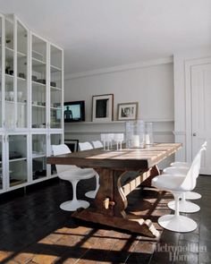 Love the modern chairs against the farm table. Love the way the space was divided with the glass book case.