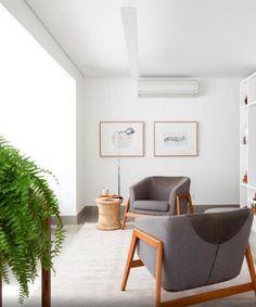Pontos sutis de madeira aquecem a sala do apartamento Alto do Ipiranga, onde predominam o branco e o cinza. Também são focos de cor viva as plantas de meia-sombra, com destaque para as samambaias. Viçosas, elas reforçam o toque natural no projeto de interiores
