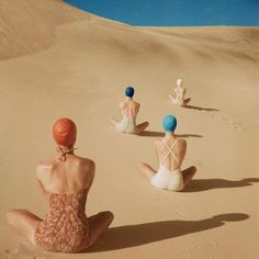 Back view of Women wearing bathing suits and sitting on a sand dune art