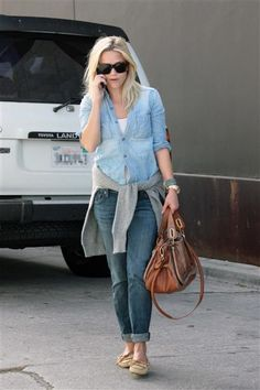 Reese wears denim on denim in the absolute best way. She paired a light chambray top with a pair of darker-wash boyfriend jeans, flats and a gray sweater wrapped around her waist.