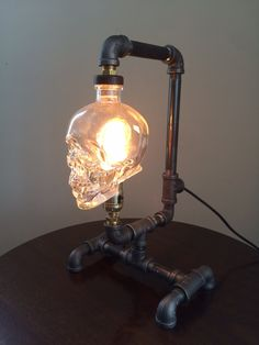 Crystal Head Vodka desk lamp. Push socket lamp with 25 watt Edison style filament bulb Black iron pipe Crystal head glass skull  10 inches wide 10.5 inches long 17 inches high 7+ foot lamp cord        Hand made in Maine by Matthew Jameson