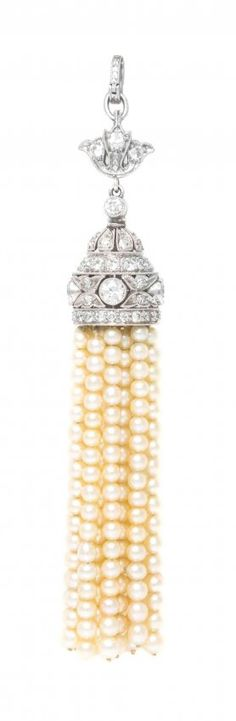 A Platinum, Diamond and Pearl Tassel Pendant, consisting of an intricate openwork hinged double sided pendant with millegrain accents and containing numerous old European and single cut diamonds weighing approximately 1.33 carats total suspending a fringe composed of 15 strands of pearls (origin not tested) measuring approximately 2.53-2.60 mm in diameter.