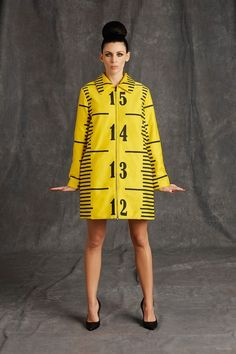 """While Moschino's last preseason under Jeremy Scott featured touches of pop art, pre-fall 2015 was all about glossy fashion with unfinished, sewing pattern elements. Blown-up rulers or guides with dashed lines bring a how-to element to the 60s inspired shapes. Liberty Ross models the collection which features a color palette of mostly black, white and yellow with bold pastels injected throughout. Playful touches such as dresses that read: """"I ..."""
